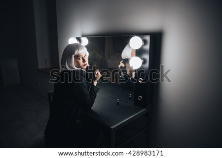 Pensive woman in blonde wig sitting near the mirror with bulbs in dressing room
