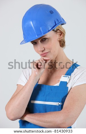 Pensive woman in overalls and a hard hat - stock photo