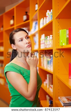 Pensive woman in pharmacy thinking while looking at shelf - stock photo