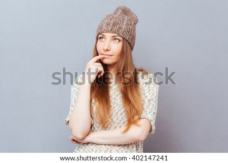 Pensive woman looking away over gray background - stock photo
