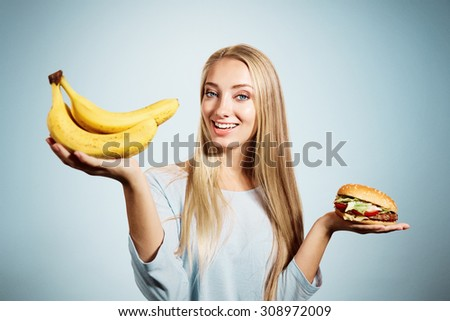 Pensive woman making decision between healthy food and fast food, over blue background - stock photo