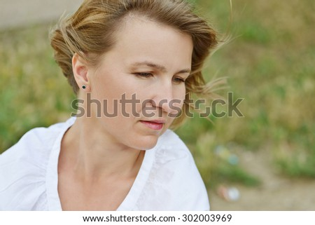 pensive woman  outdoors in the summer time - stock photo