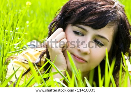Pensive woman portrait over the grass - stock photo