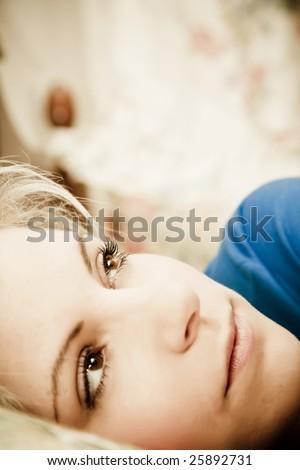 Pensive woman portrait still in bed. Focus on upper eye. - stock photo