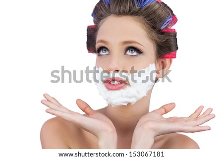 Pensive woman posing with shaving foam on face on white background - stock photo