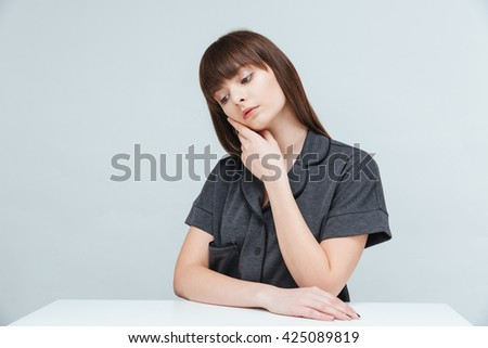 Pensive woman sitting at the table isolated on a white background - stock photo