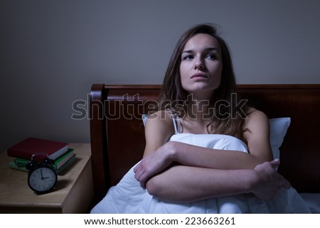 Pensive woman stying sleepless in bed at night - stock photo
