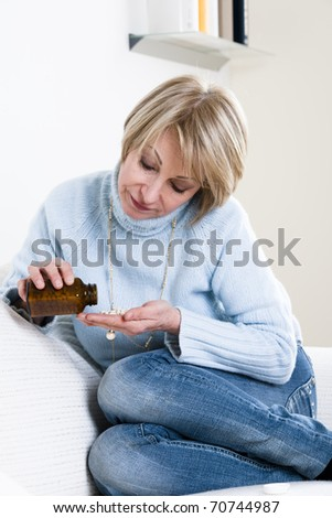 Pensive Woman Taking Pills - stock photo