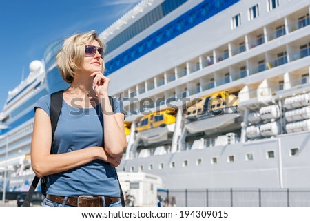 Pensive woman tourist with backpack on shore, standing in front of big cruise liner, dreaming about cruising - stock photo