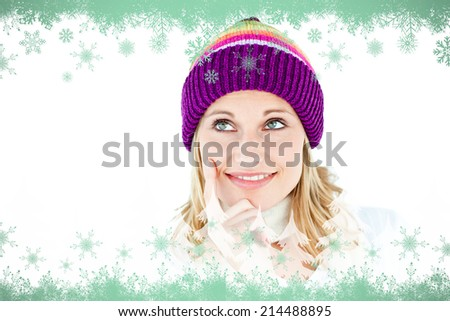 Pensive woman with a colorful hat against green snowflake design