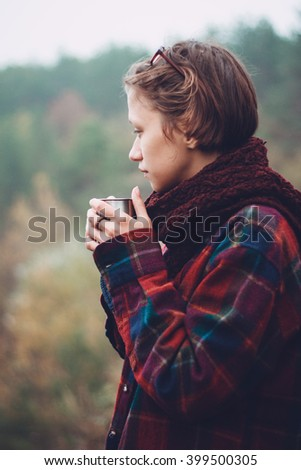 Pensive woman with cup of tea at outdoor Woman was plunged deep in thought and was lost in contemplation. She is drinking tea and enjoying the beautiful scenic view.  - stock photo