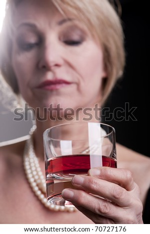 Pensive Woman With Drink, black background - stock photo