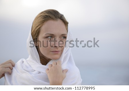 pensive woman with head scarf on the beach - stock photo