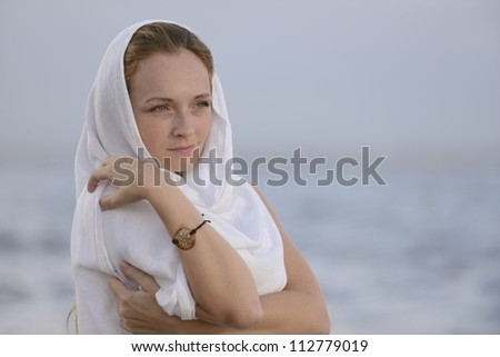 pensive woman with head scarf on the beach