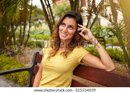 Pensive woman 20-24 years old looking away while sitting on bench outdoors - stock photo