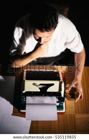 Pensive Writer novelist working on a book using typewriter