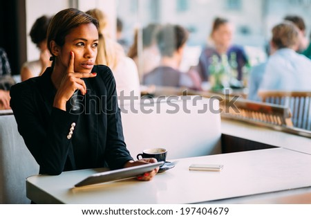 Pensive young black woman using tablet computer in coffee shop - stock photo