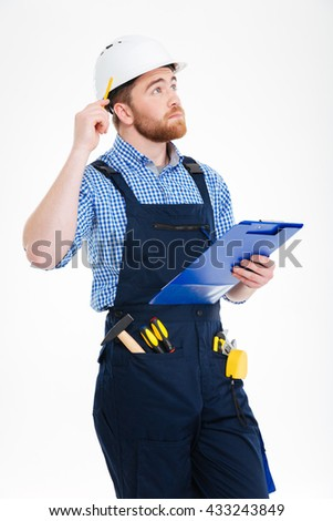 Pensive young builder in helmet thinking and writing on clipboard - stock photo