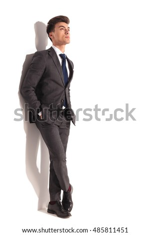 pensive young business man standing with hands in pockets and looks up to something against white wall