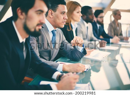 Pensive young businessman listening to explanations at seminar surrounded by other listeners - stock photo