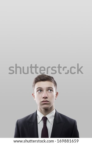 pensive young businessman on dark space background - stock photo
