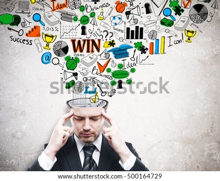 Pensive young businessman with colorfulbusiness sketch coming out of his head on concrete background. Brainstorming concept
