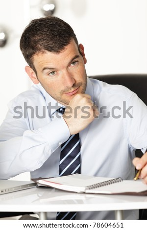 pensive young businessman with pen in office - stock photo