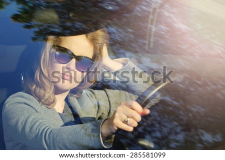 Pensive young businesswoman in a car stuck in traffic - stock photo