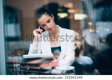 Pensive young businesswoman using tablet computer in cafe - stock photo