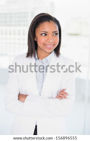 Pensive young dark haired businesswoman posing with arms crossed in bright office