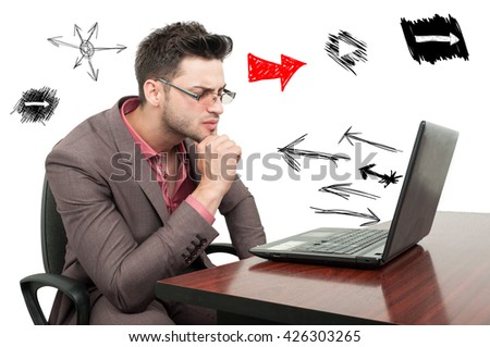 Pensive young employee trying to solve a business problem sitting on his desk with arrows around him - stock photo