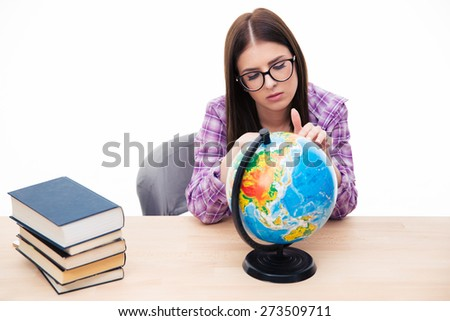 Pensive young female student sitting at the table with globe over white background - stock photo