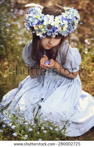 pensive young girl in a wreath of blue flowers - stock photo