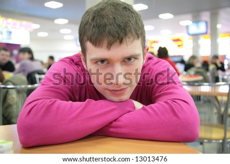 pensive young man at table in cafe