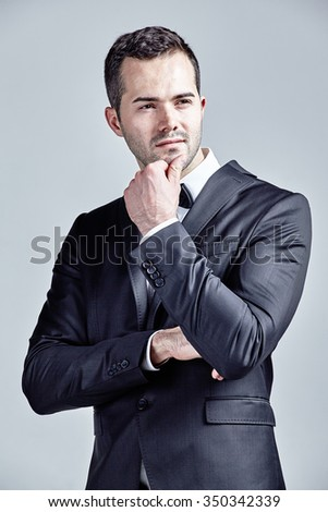 Pensive young man isolated over grey - stock photo