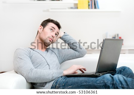 Pensive young man looking up while working on laptop at home - stock photo