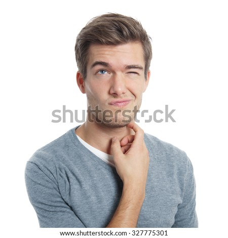 pensive young man scratching his head squinting and looking up - stock photo