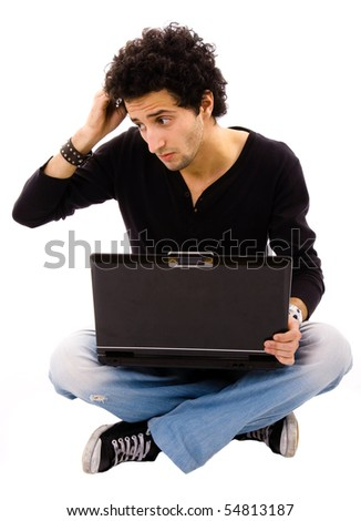 Pensive young man sitting on floor using laptop, isolated on white