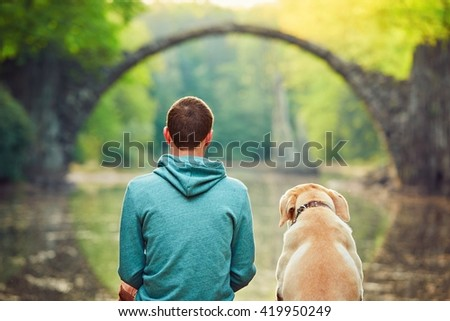 Pensive young man sitting on the pond bank with a his dog - Amazing place in Germany. Rakotzbrucke also known as Devils Bridge in Kromlau.  - stock photo