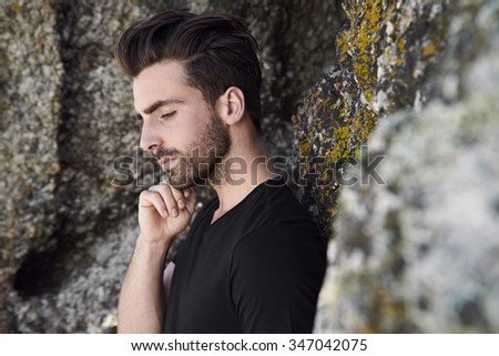 Pensive young man thinking against rocks - stock photo