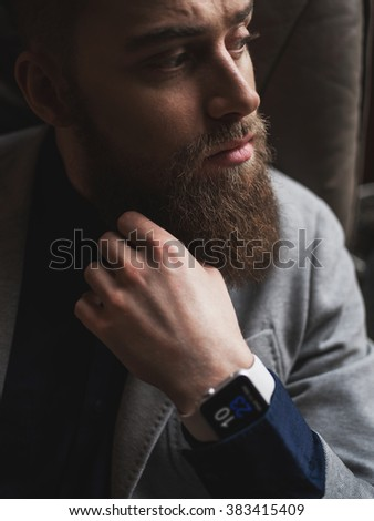 Pensive young man with beard is thinking - stock photo