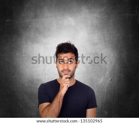 Pensive young men in black over a irregular gray background - stock photo