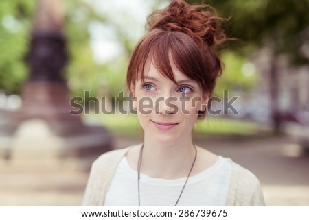 Pensive young redhead woman standing outdoors in an urban park looking to the side with a quiet smile and thoughtful expression - stock photo