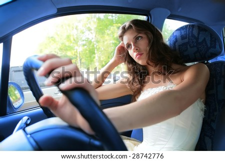 pensive young woman drive a car - stock photo