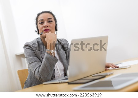 Pensive young woman in office thinking with headset on. She is looking at camera behind her laptop computer on wood desk. - stock photo