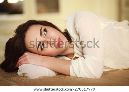 Pensive young woman lying on the bed at home in sunny daylight - stock photo