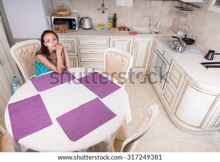 Pensive Young Woman Sitting at the Table Alone in the Home Kitchen - stock photo