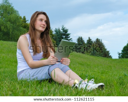 Pensive young woman sitting on green grass staring into the distance while holding a tablet on her knees