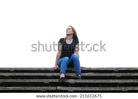 pensive young woman sitting on outside flight of stairs - stock photo