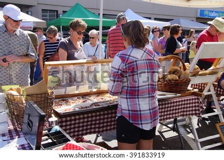 PENTICTON, BRITISH COLUMBIA - JUN 20, 2015 - Woman serving pastries at the  Saturday Market,  Penticton, British Columbia, Canada - stock photo